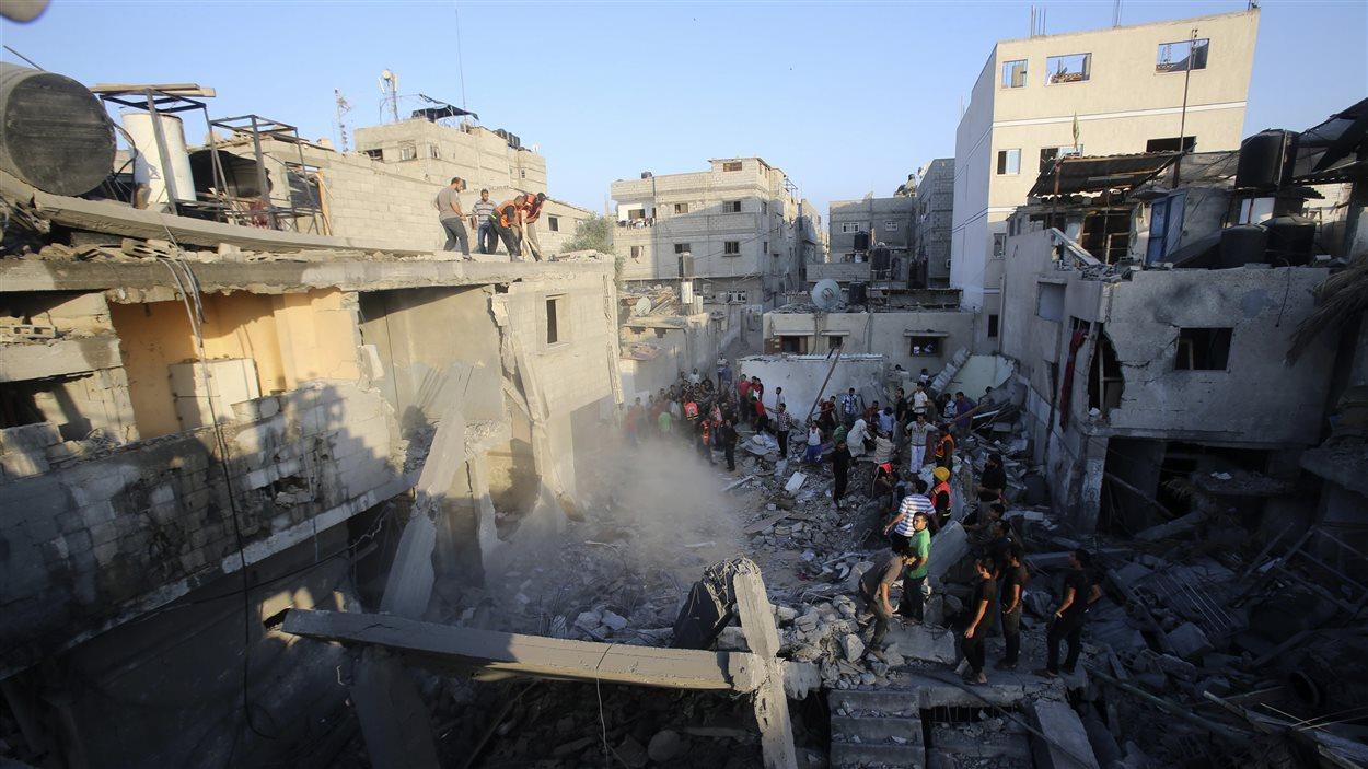 Des secouristes s'affairent dans les ruines d'une maison de Khan Younès, dans la bande de Gaza, détruite par un bombardement israélien, selon les services de police.