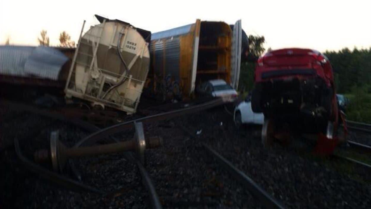 Plusieurs voitures que transportait le train sont lourdement endommagées.