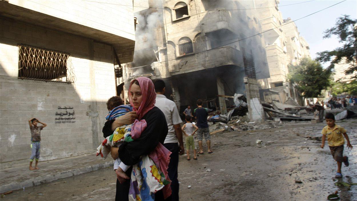 Une Palestinienne fuit un bombardement avec son enfant dans les bras dans la ville de Gaza.