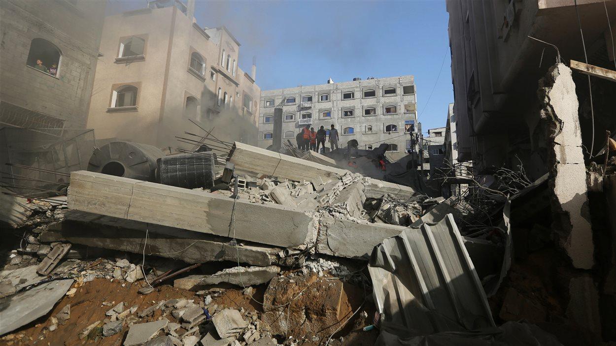 Des Palestiniens inspectent les décombres d'une maison touchée par un missile israélien lancé sur la bande de Gaza, jeudi.