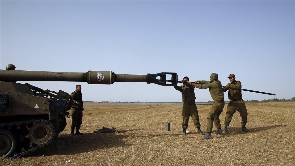 (12 juillet 2014) Des soldats israéliens nettoient le canon d'un de leur appareil d'artillerie lourde, placé à l'extérieur de la bande de Gaza.