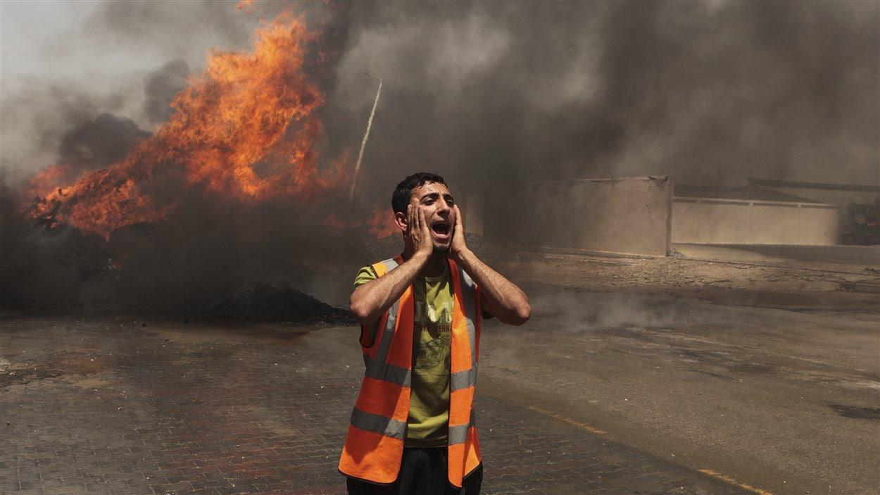 (12 juillet 2014) Un Palestinien hèle les pompiers près d'un feu qui aurait été causé par un bombardement israélien, selon la police, dans l'est de Gaza, le 12 juillet 2014
