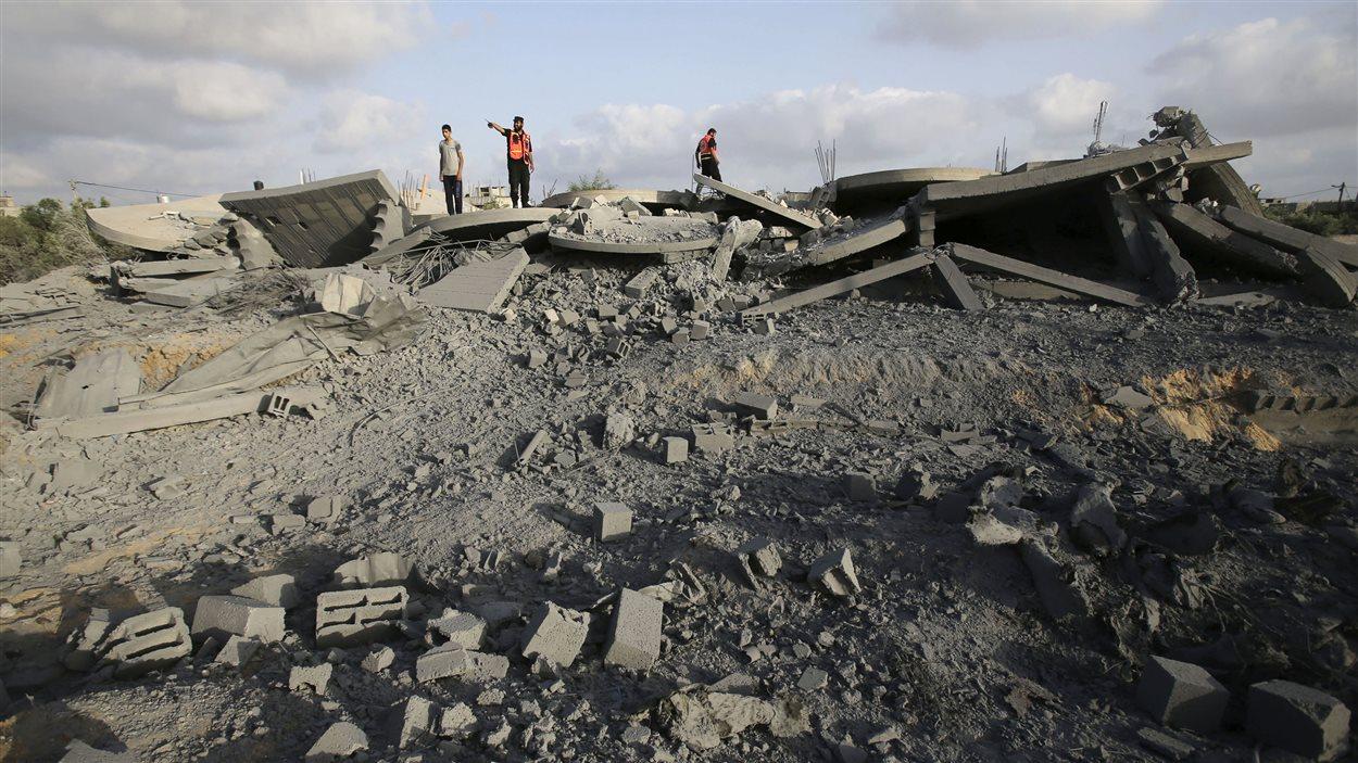 (13 juillet 2014) Des Palestiniens fouillent dans dans ce qu'il reste d'une maison qui, selon les policiers, a été détruite par un raid israélien.