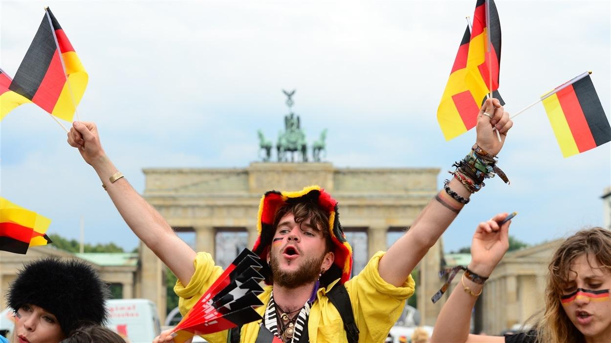 Un partisan allemand devant la porte de Brandebourg dimanche à Berlin.