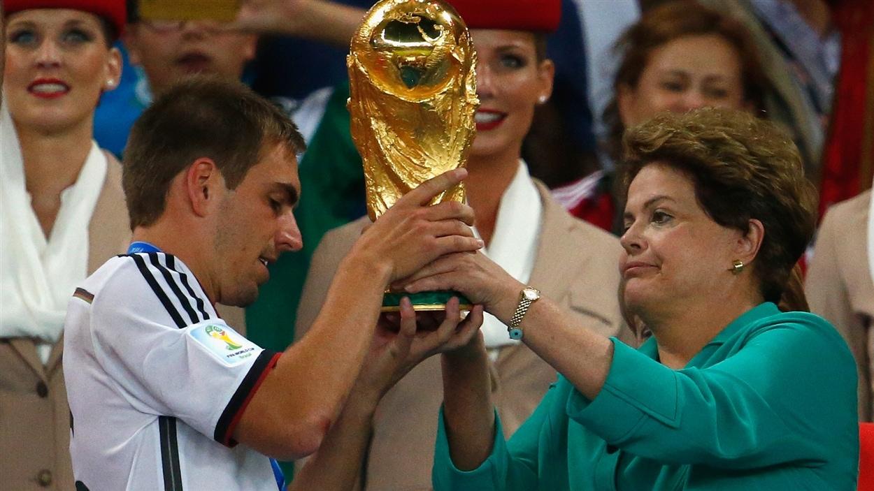 Philipp Lahm reçoit le trophée de la Coupe du monde des mains de la présidente brésilienne Dilma Rousseff.