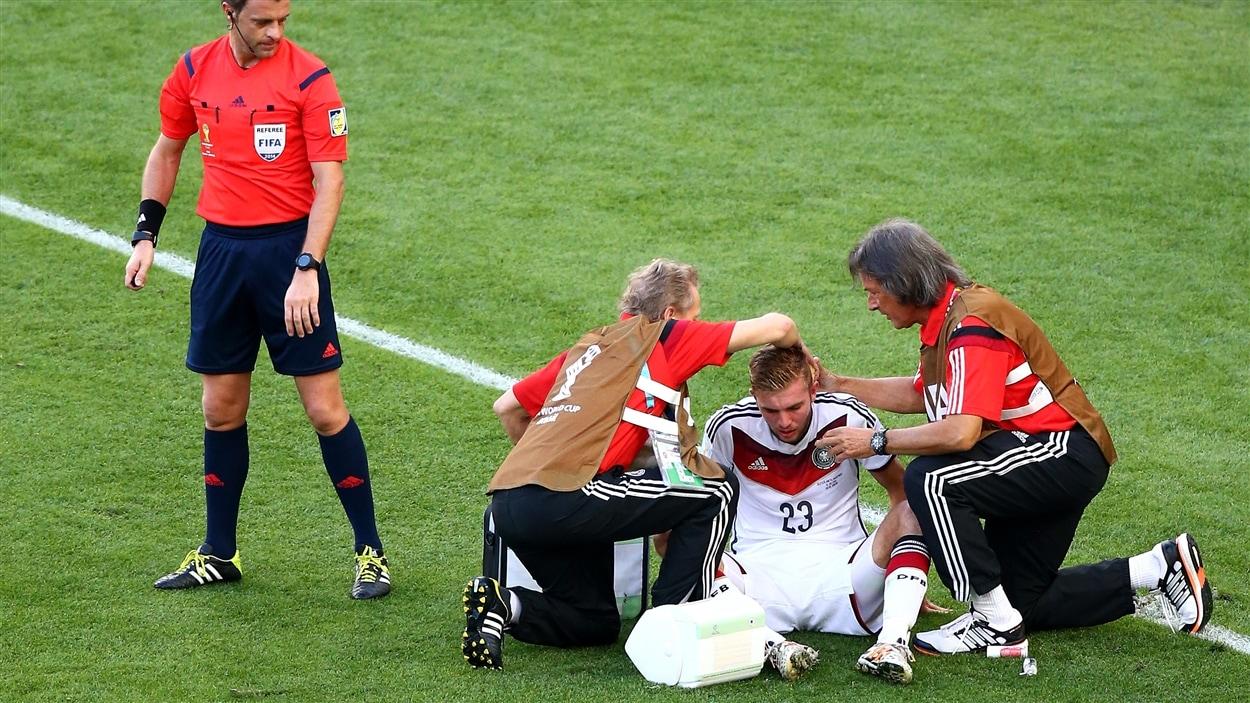 Deux soigneurs s'occupent de l'Allemand Christoph Kramer qui vient d'être frappé à la tête en première demie.