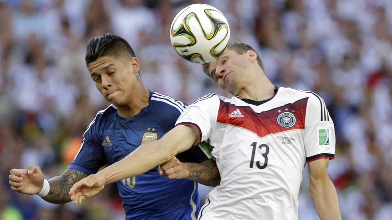 L'Allemand Thomas Müller contrôle le ballon de la tête malgré les efforts de Marcos Rojo.