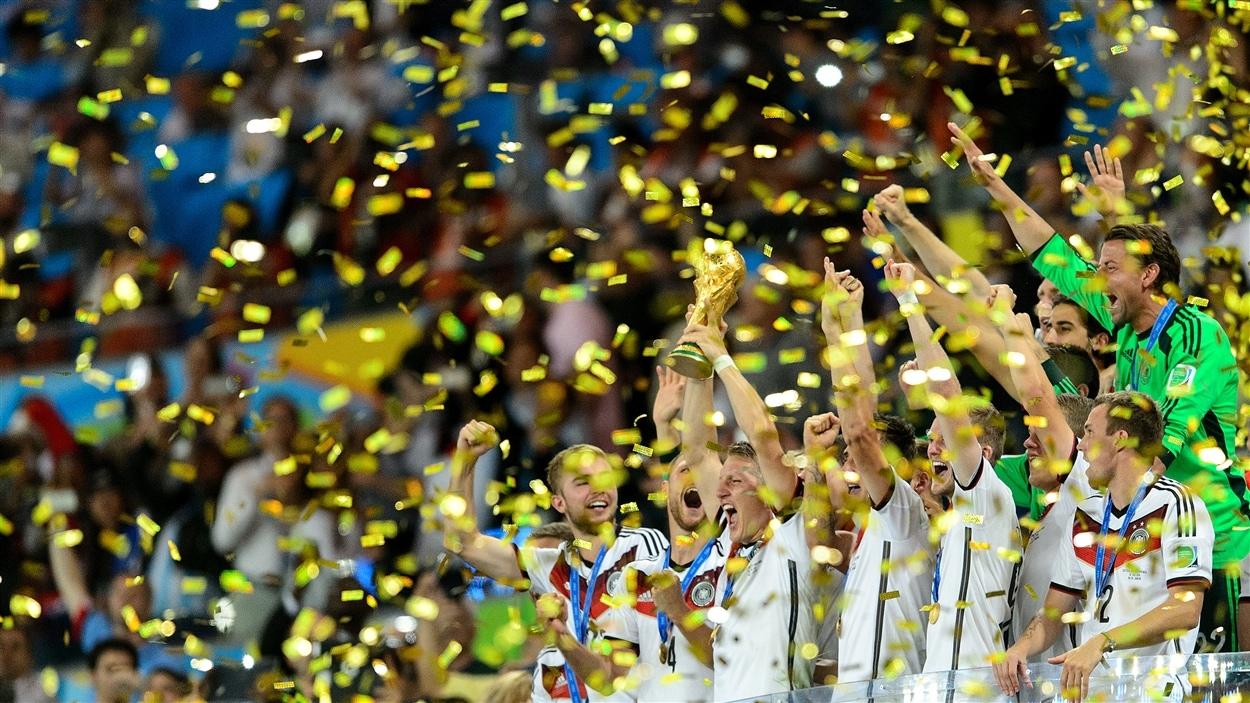 Victoire ! Les joueurs allemands brandissent le trophée de la Coupe du monde.