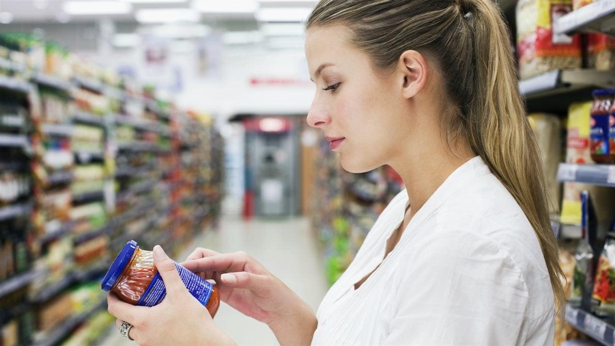 Une consommatrice lit l'étiquette d'un produit à l'épicerie.