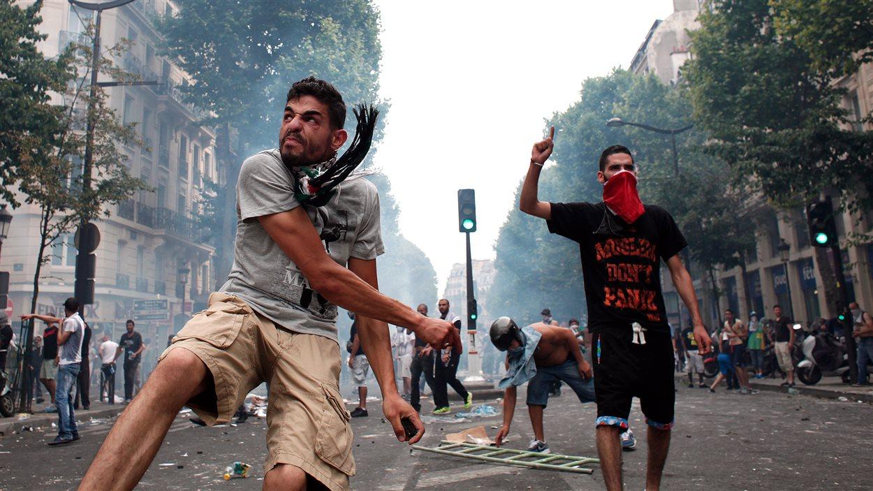 Des manifestants propalestiniens jetant des roches en direction des policiers, à Paris, le 19 juillet 2014