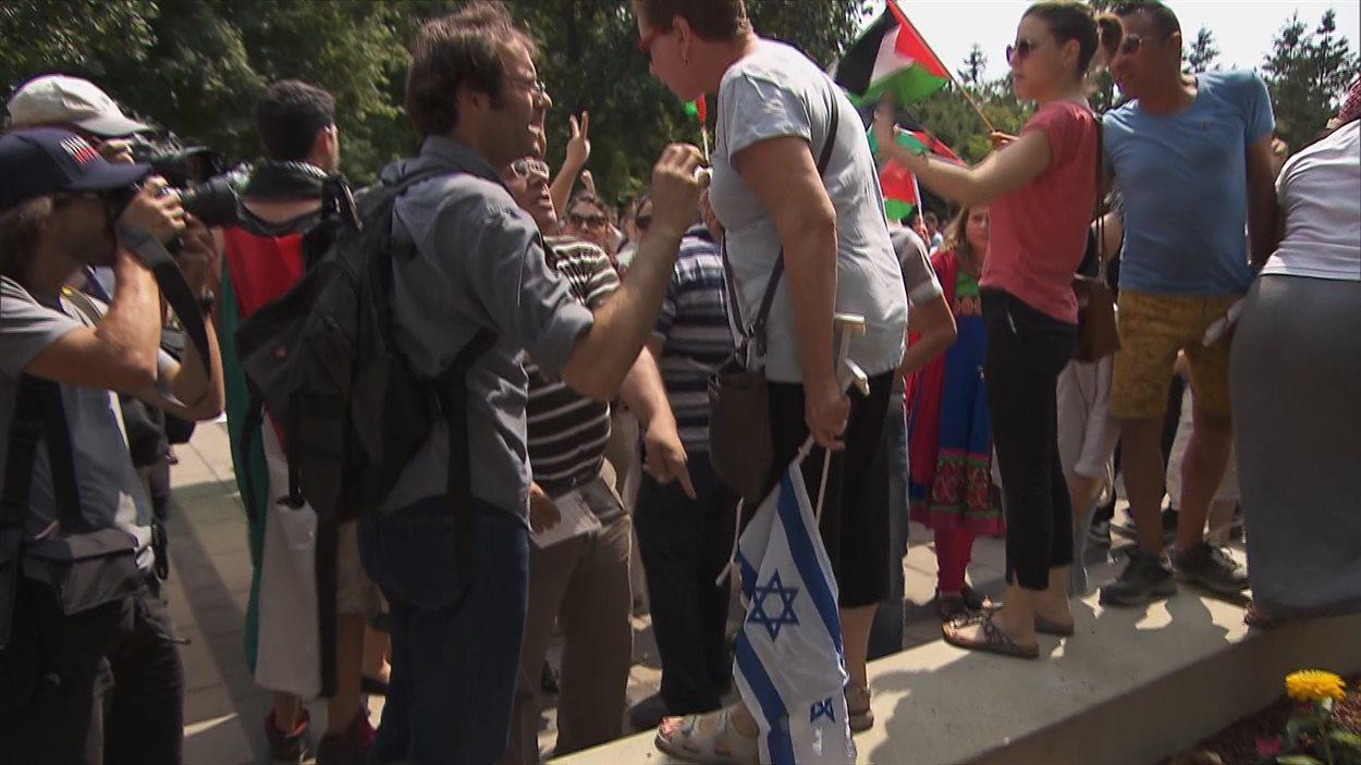 Une dame avec un drapeau israélien a été bousculé par quelques militants pro-palestiniens à Montréal.