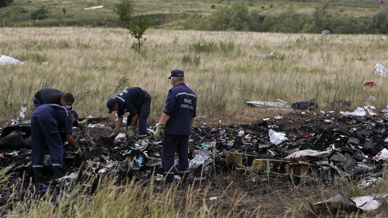 Des enquêteurs ukrainiens au site de l'écrasement de l'avion MH17.