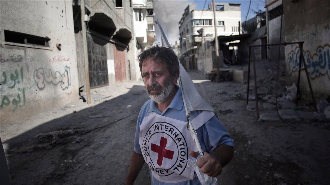 Un homme de la Croix-Rouge internationale brandit un drapeau blanc pendant l'évacuation.