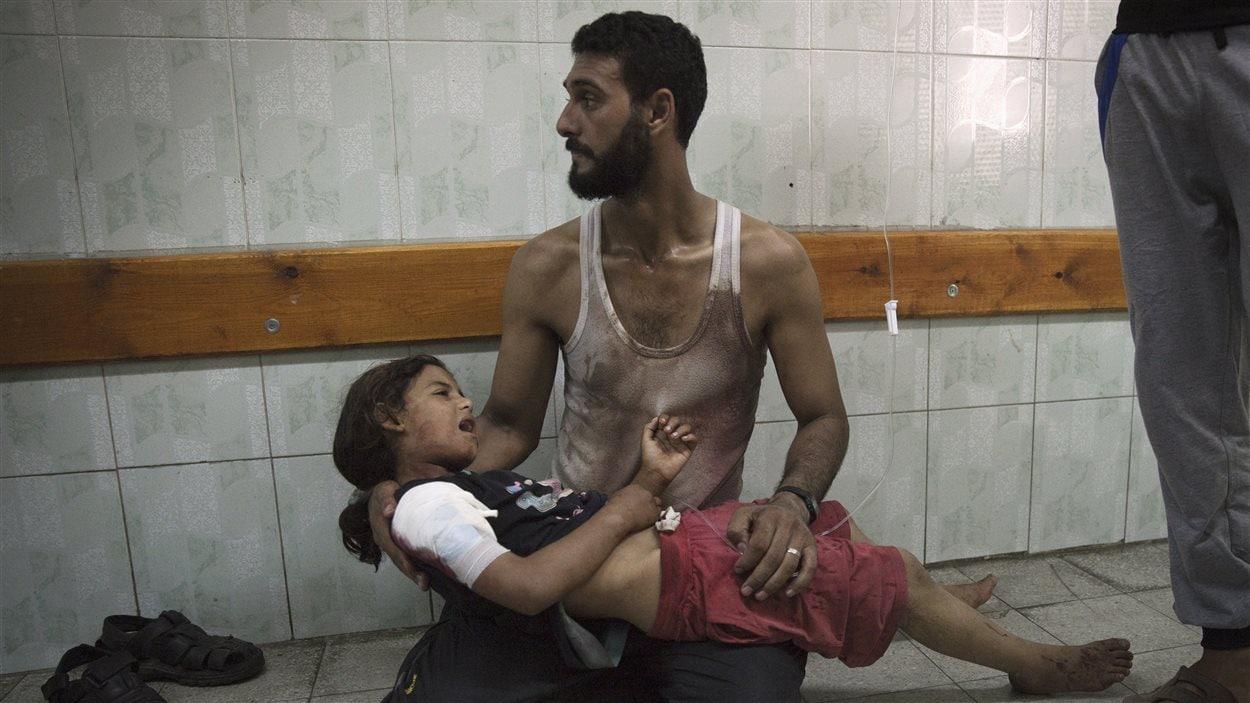 Un homme tient dans ses bras sa fille blessée lors du bombardement de l'école de l'ONU où ils s'étaient réfugiés.