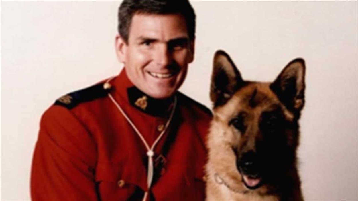 Le caporal et maître-chien Ken Barker, de la Gendarmerie royale du Canada, pose avec un chien.