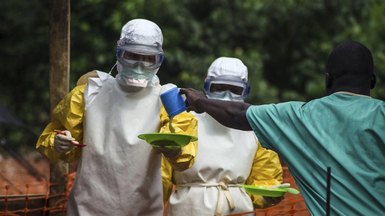 Au Sierra Leone, des employés de Médecins sans frontières donnent à manger à des patients mis en isolation.
