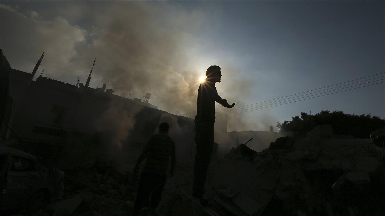 Un Palestinien se tient sur les décombres d'une maison qui aurait été détruite par un tir israélien, à Gaza.