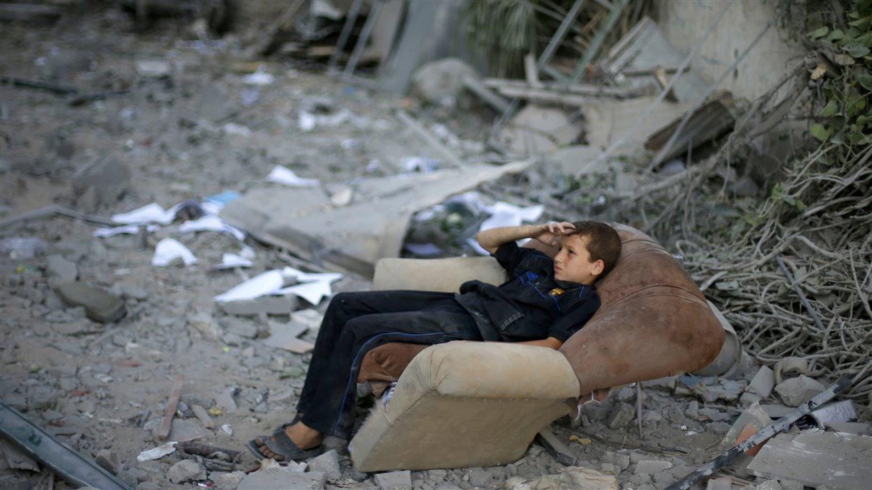 Un jeune Palestinien s'est assis sur un sofa, le 2 août, à côté de ce qui était autrefois la maison familiale.
