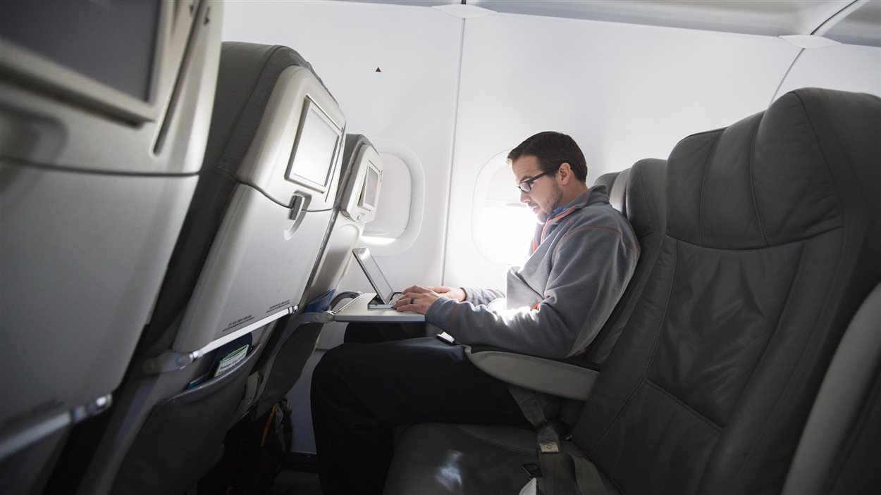 Un homme utilise son ordinateur à bord d'un avion.