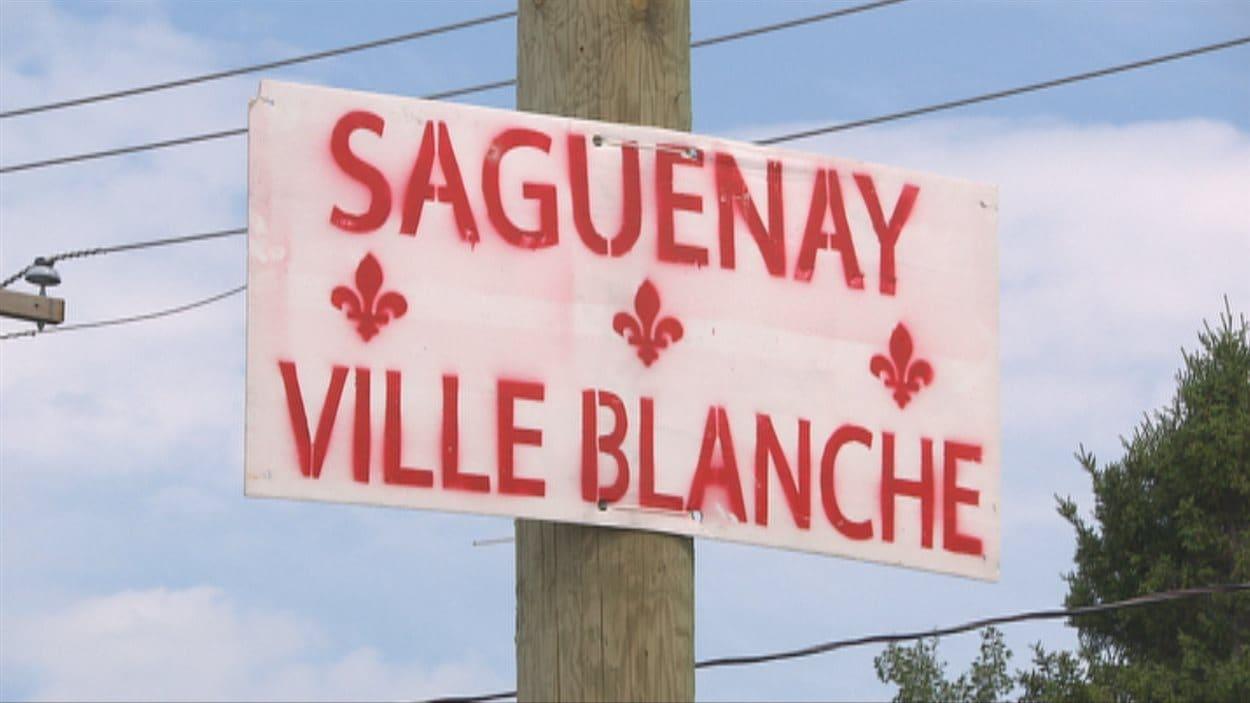 """Des affiches portant l'inscription """"Saguenay ville blanche"""" ont été apposées à l'entrée de la ville."""