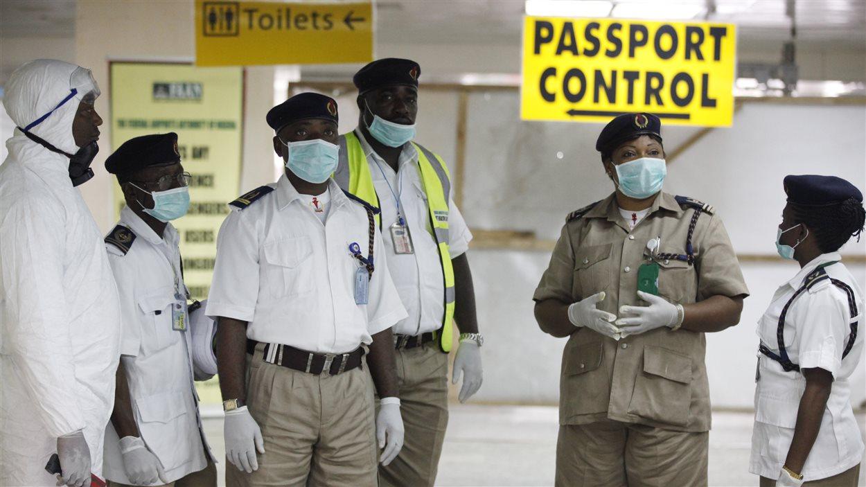 Des responsables de la santé contrôlent des passagers à l'aéroport international de Lagos, au Nigeria, où une personne est morte de l'Ebola.