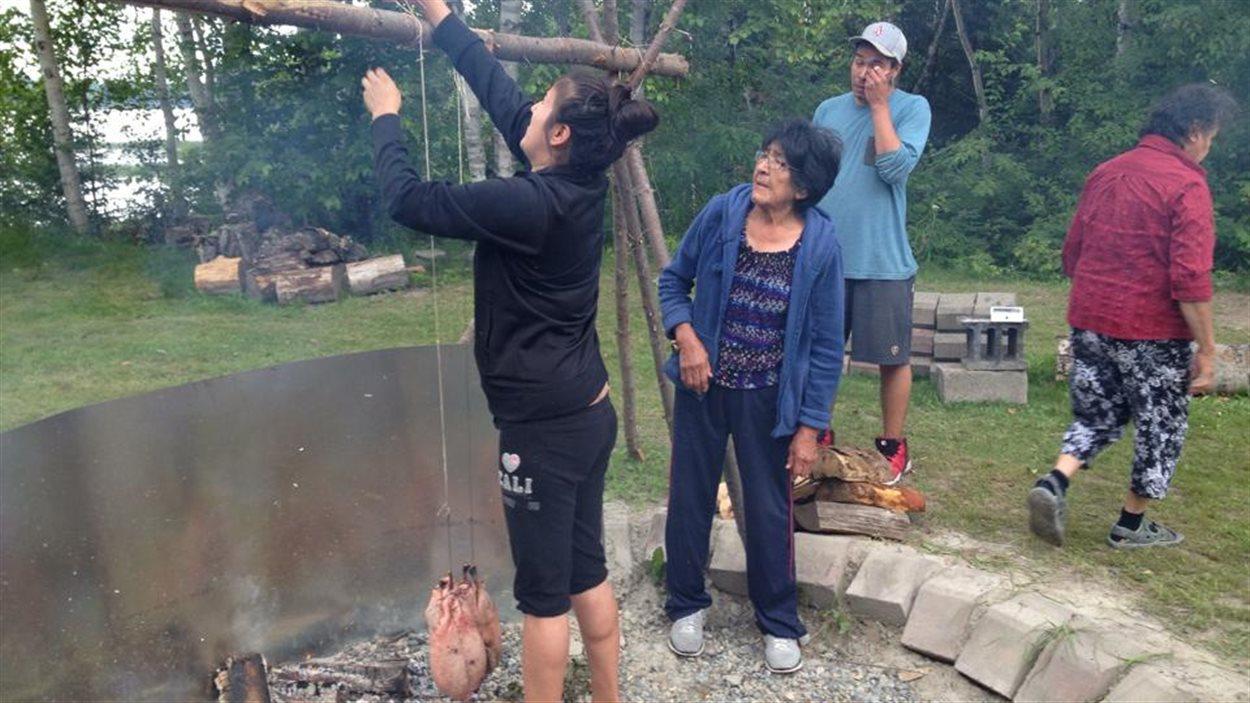 Vera Pien accroche l'outarde qu'elle a préparée pour la faire cuire au-dessus de la braise