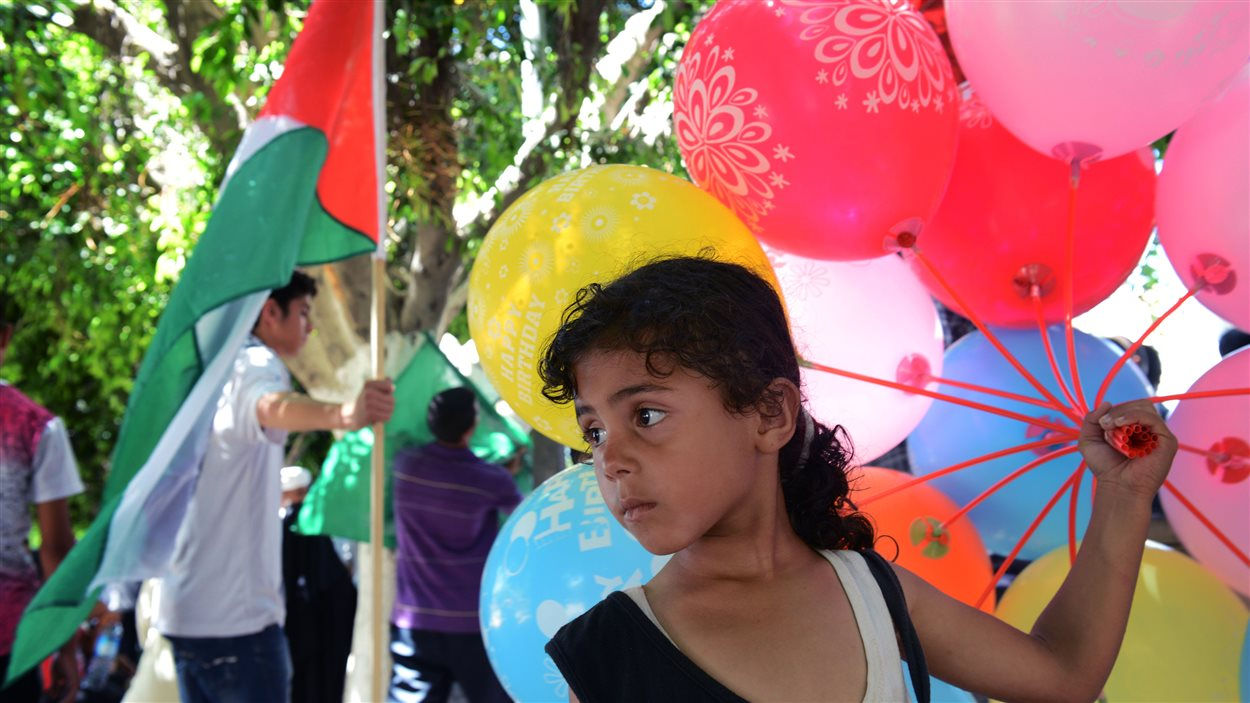 Une jeune palestinienne vend des ballons dans le cadre d'une manifestation d'appui au Hamas qui a eu lieu jeudi à Gaza.