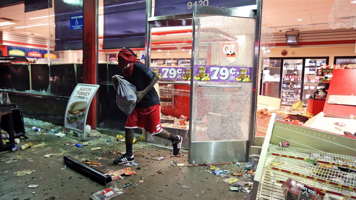 Des manifestants ont pillé des magasins dimanche soir lors d'une émeute à la suite de la mort d'un adolescent noir.