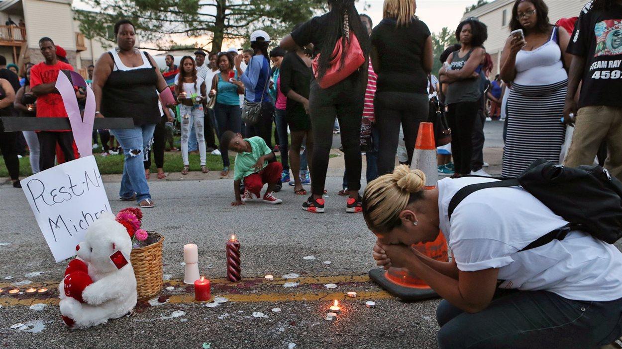 Une femme se recueille à l'endroit où Michael Brown a été tué samedi.