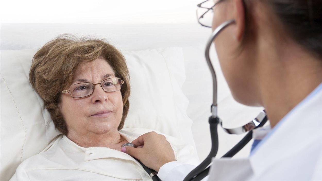 Une femme est ausculté par un médecin