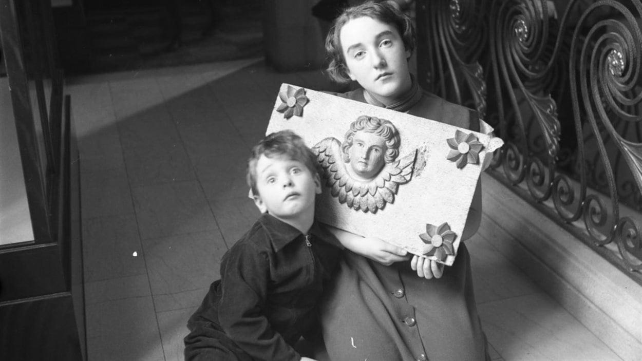 Lida Moser : Deux jeunes élèves de L'École Moderne posant avec un bas-relief de la collection Paul Gouin, au Musée de la province, à Québec, automne 1950, image d'après un négatif original (6 x 6 cm), (P728,S1,D1,PWQ-143)