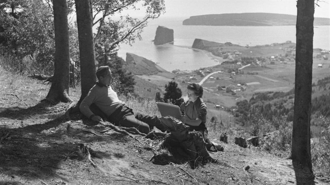 Lida Moser, L'artiste Suzanne Guité réalisant un portrait de son mari, Alberto Tommi, au Pic de l'Aurore, à Percé. Négatif sur acétate, 6 cm x 6 cm. (P728,S1,D1,P13-11)