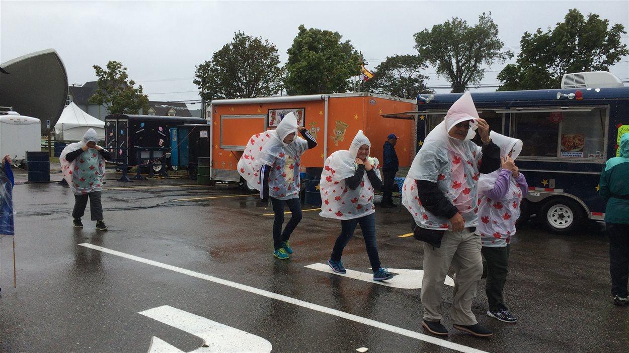 Des participants affrontent la pluie en prévision des activités du 15 août, à Caraquet