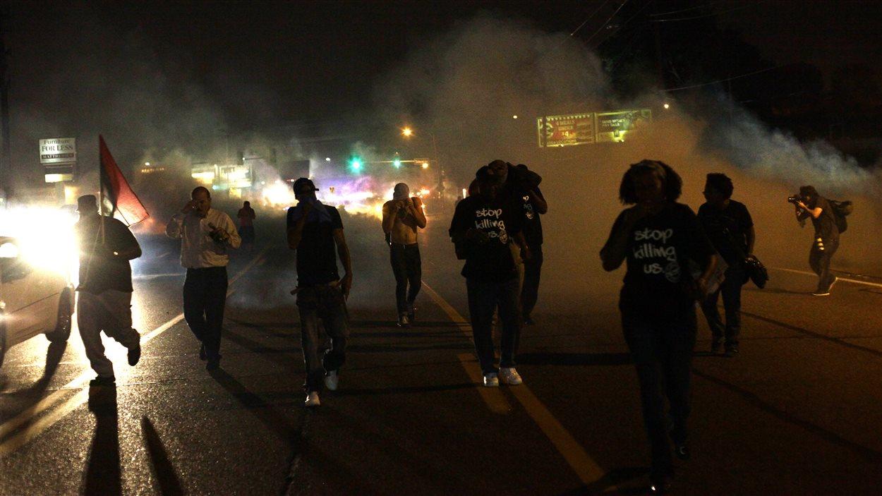 Des manifestants se dispersent après que la police eut lancé des gaz lacrymogènes et des fumigènes, dimanche, avant même le début du couvre-feu.
