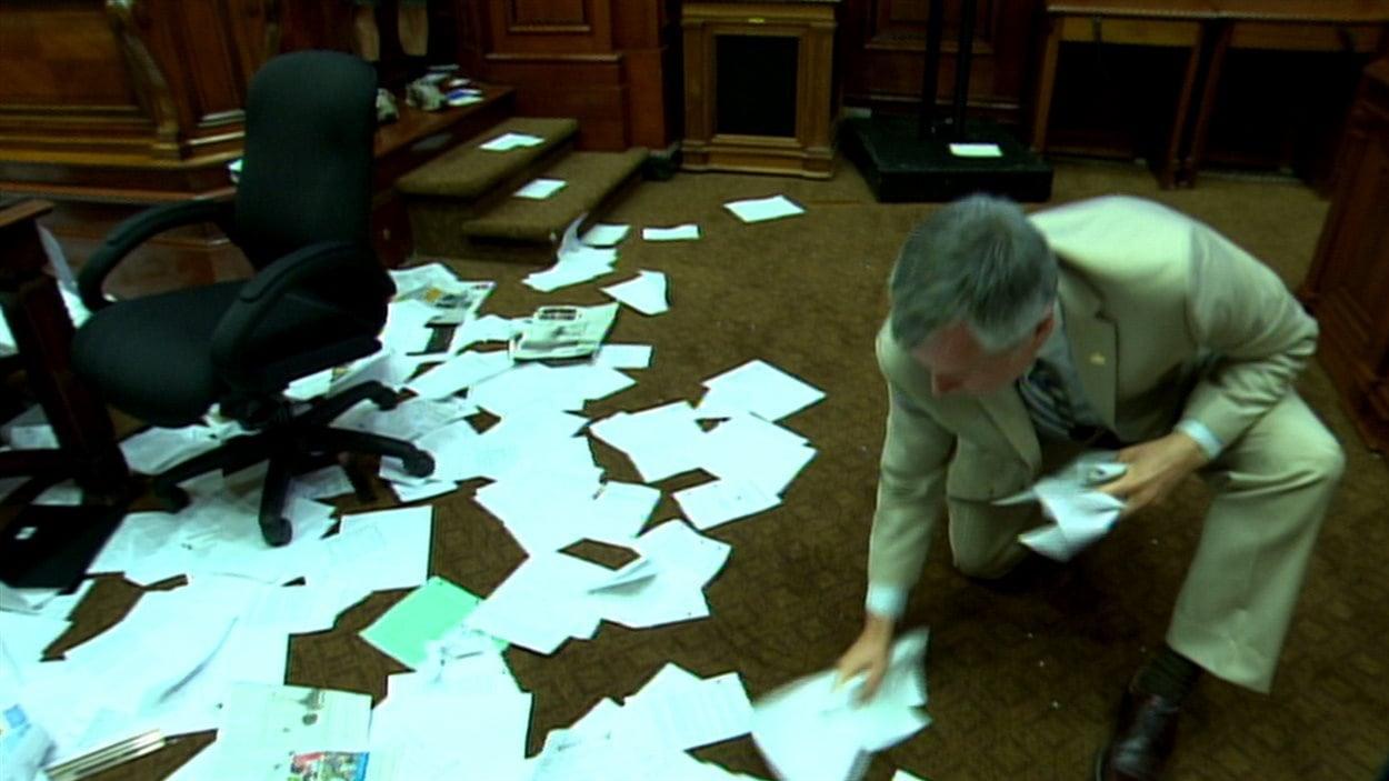 Un employé ramasse les papiers laissés par les manifestants à l'hôtel de ville de Montréal, le 18 août 2014.