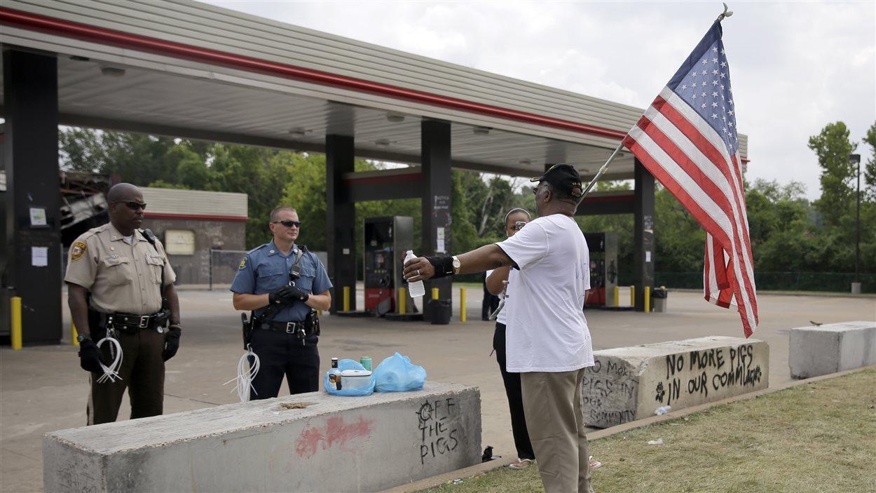 Un homme portant un drapeau américain discute avec des policiers près d'une station-service de Ferguson.