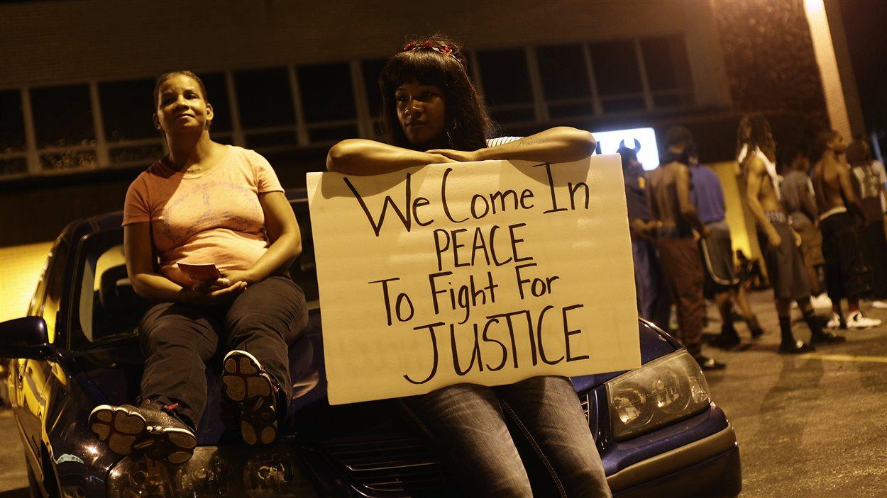 Une manifestante tient une affiche sur laquelle on peut lire « Nous venons en paix nous battre pour la justice », le 19 août 2014.