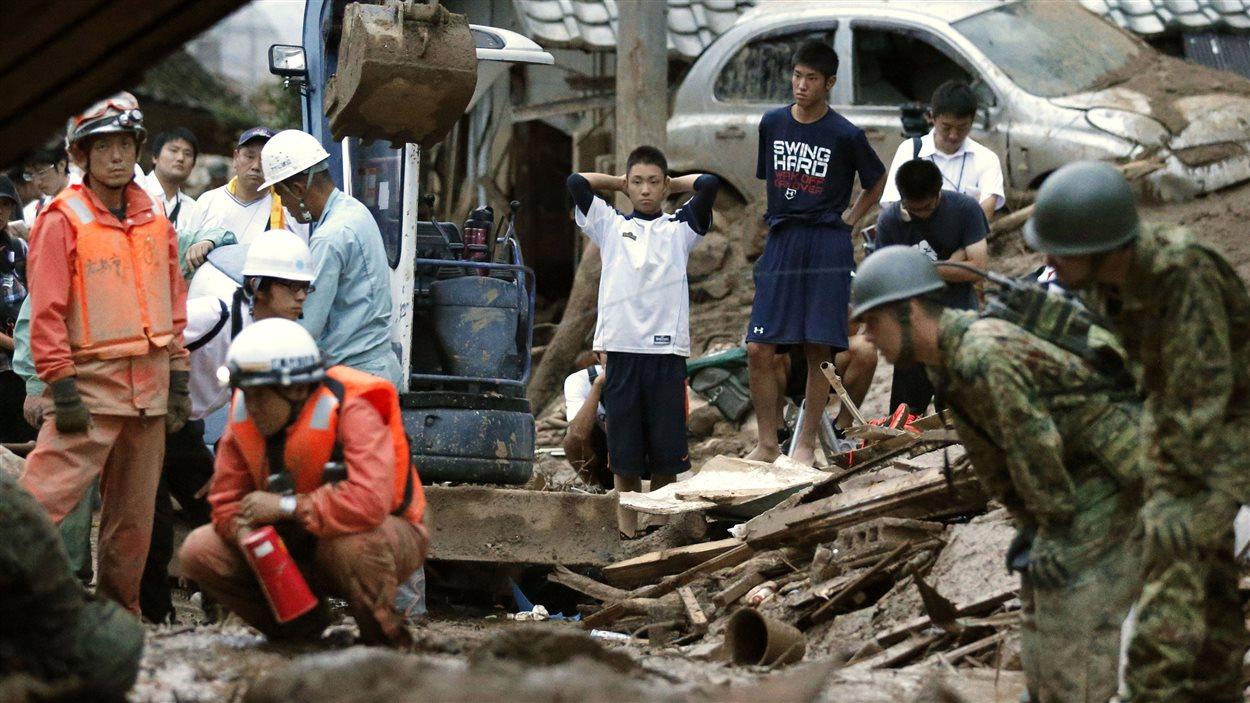 Des secouristes tentent de trouver un jeune garçon qui serait enseveli sous les décombres, sous le regard attentif de camarades de classes.