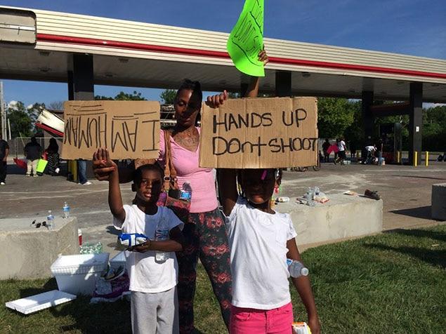 On peut lire sur les pancartes de ces deux enfants : «Je suis humain» et «Les mains en l'air, ne tirez pas».
