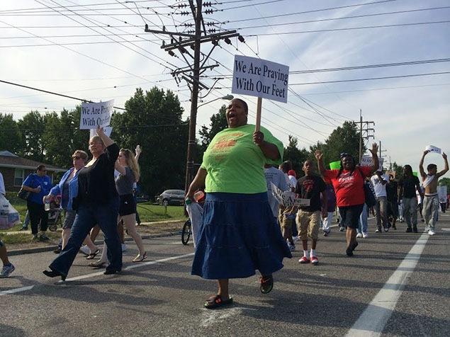 Au cours d'une marche de protestation à Ferguson, plusieurs manifestants brandissent des pancartes où l'on peut lire : «Nous prions avec nos pieds».
