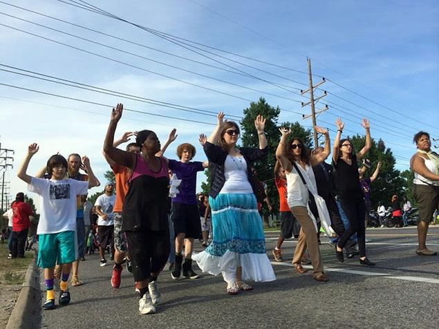 Blancs et Noirs marchent côte à côte en mettant, symboliquement, les mains en l'air.