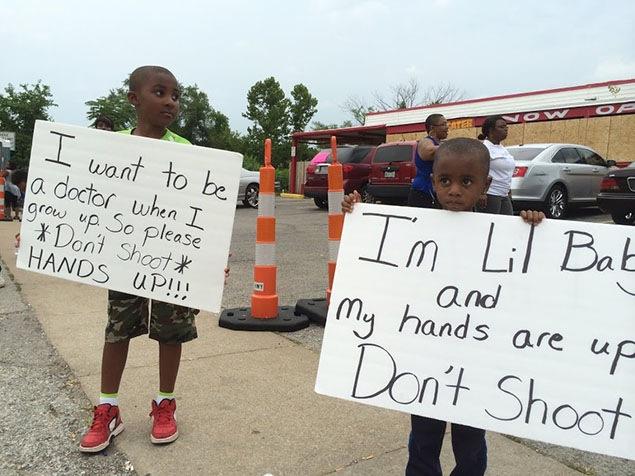 L'un dit qu'il veut être docteur quand il sera grand, et donc, de ne pas le tirer. Sur l'autre pancarte, on dit «Je ne suis qu'un petit bébé et mes mains sont en l'air. Ne tirez pas».