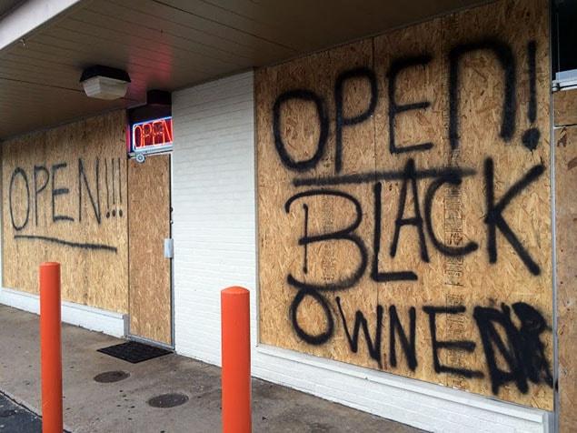 La mort de Mike Brown ravive des tensions raciales. Ici, on peut voir, sur un commerce barricadé montrant néanmoins un signe «ouvert» allumé : «Ouvert, propriétaire noir» .