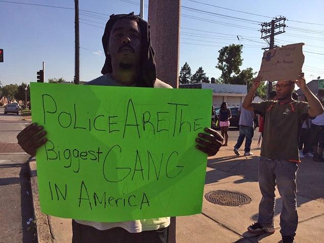 Devant l'endroit où un autre jeune noir a été abattu, mardi, à St. Louis, un homme a inscrit sur une pancarte : «La police est la plus importante gang en Amérique».