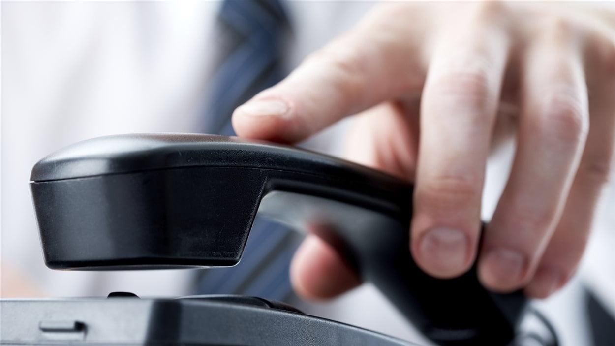 Un homme prend un téléphone.