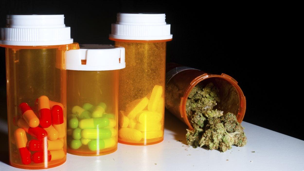 De la marijuana dans un pot de médicament à côté d'autres pots de pilules.