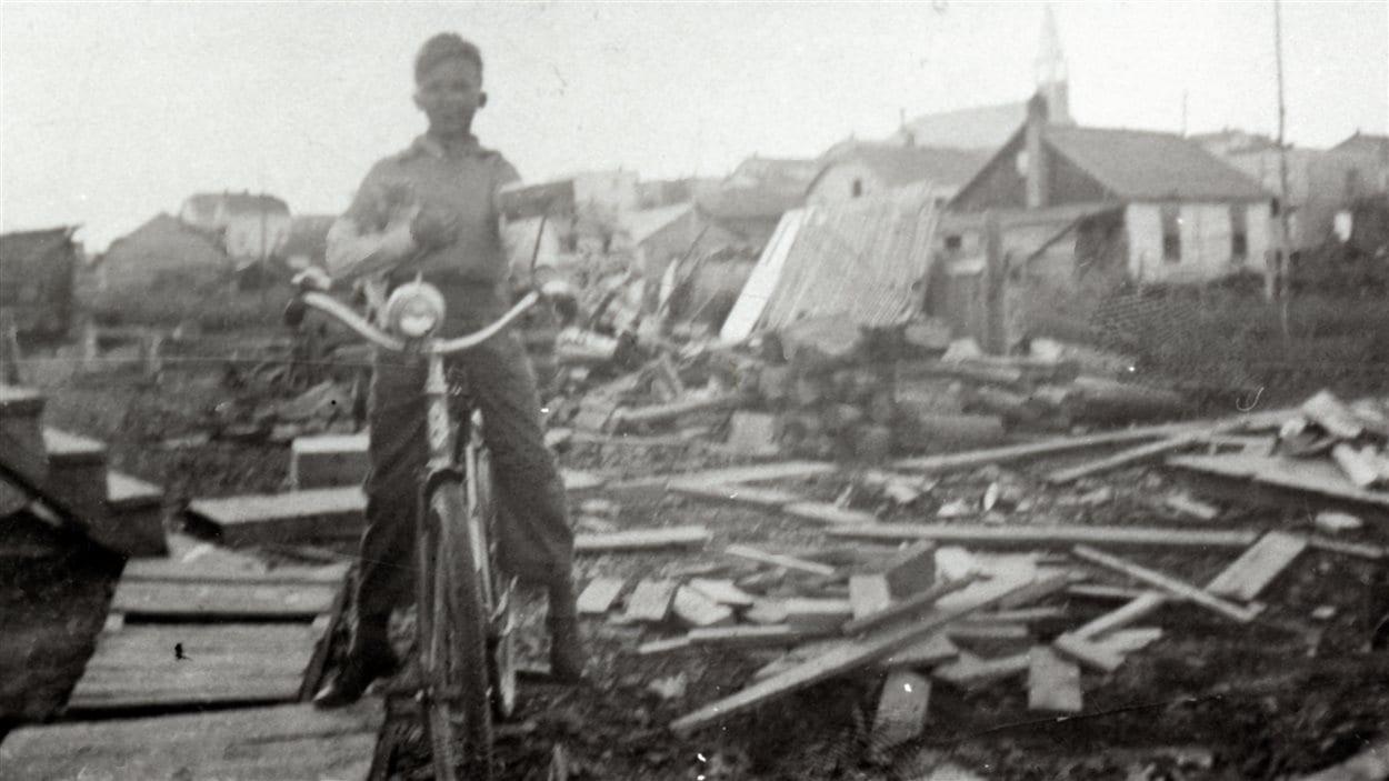 Henri Robert sur sa bicyclette lors du déménagement des maisons de Rouyn-Sud en 1938.
