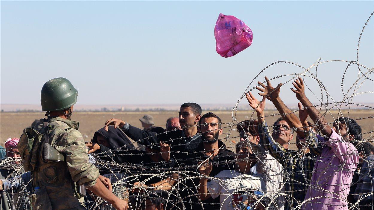Un soldat turc lance un sac rempli de bouteilles d'eau à un groupe de réfugiés kurdes en provenance de Syrie.