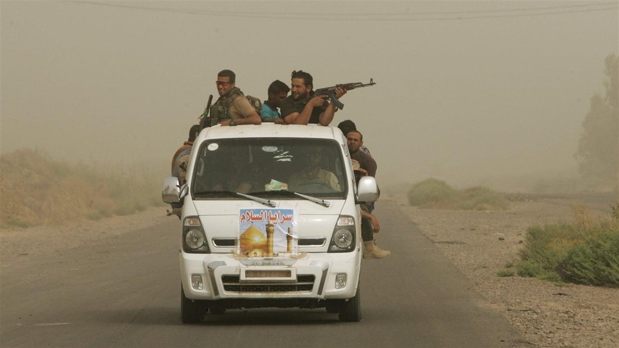Des combattants chiites irakiens avec la patrouille « Brigades de la paix » durant une tempête de sable à Samarra, en Irak, le 12 juillet dernier