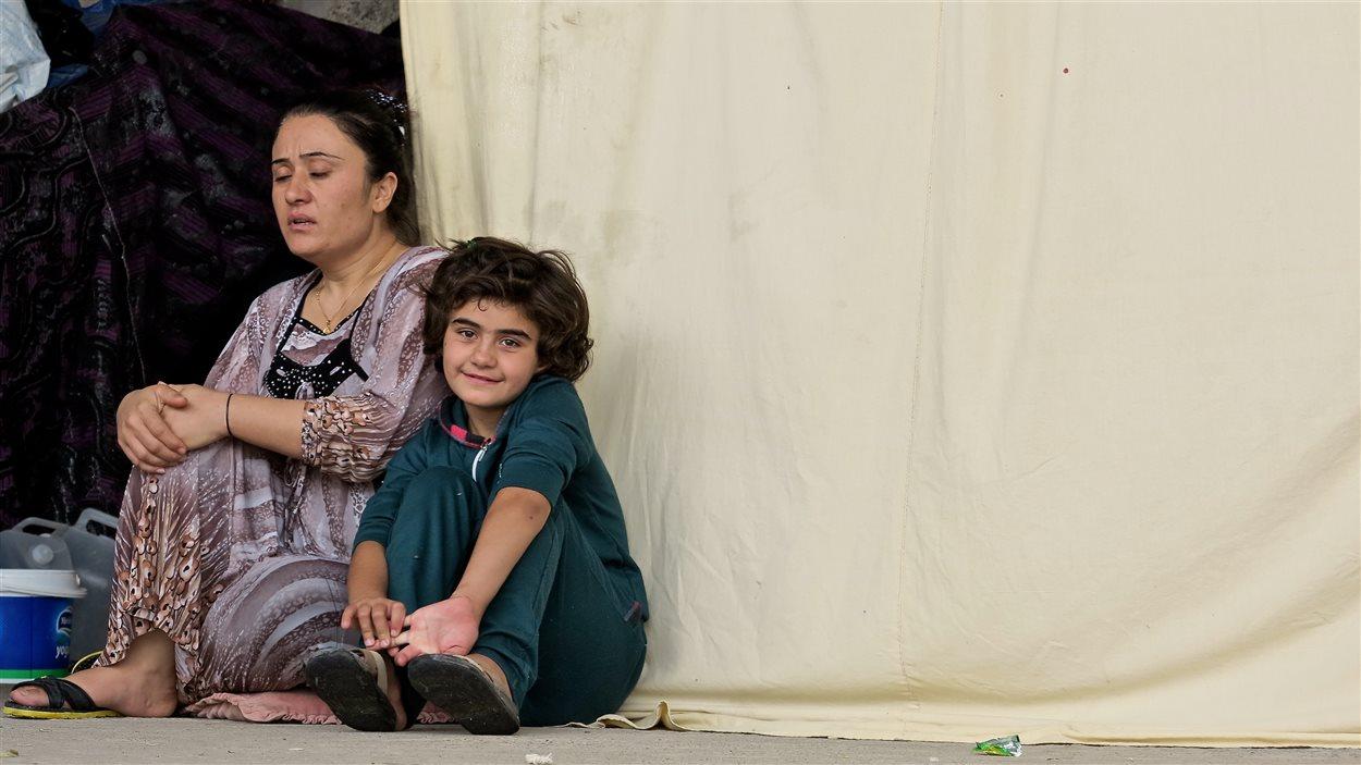 Une famille devant sa tente de réfugiés en Irak
